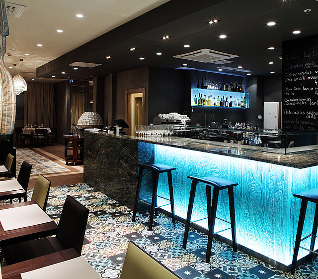 [Translate to Italienisch:] Blue-lit hotel bar at Gastronome Riga Restaurant
