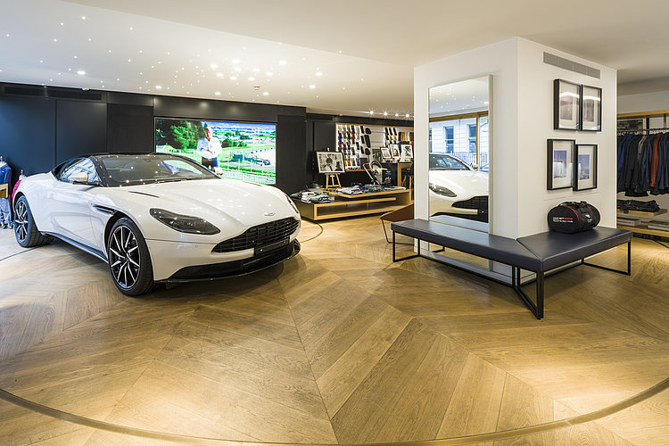 Lounge area with a white sports car on the presentation surface